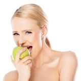 Side view of blond woman she bites an apple Royalty Free Stock Photos