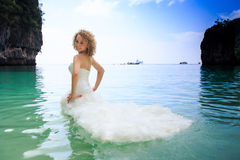 Side view blonde bride in fluffy dress in shallow azure sea Royalty Free Stock Image