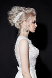 Side view of blonde bride wearing white wedding dress, shiny accessories with stylish haircut posing in dark studio. Bride haircut Royalty Free Stock Image