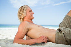 Side view of a blonde man lying on the beach Royalty Free Stock Image