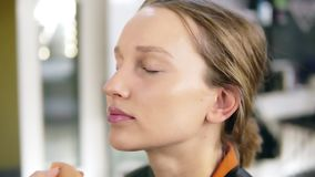 Side view of a blonde, young girl getting a make up from professional make up artist. Apply foundation with a sponge stock footage