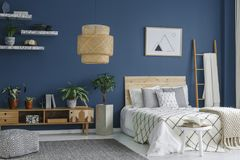 Side view of bedroom. Side view of a blue bedroom interior with a modern lamp, double bed, plants and cabinet royalty free stock image