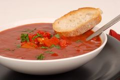 Side view of a bowl of tomato, red pepper and basil soup with br Stock Photos