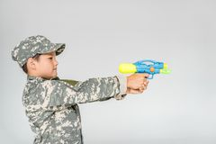 Side view of boy in camouflage clothing with toy water gun. Isolated on grey royalty free stock photography
