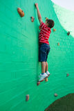Side view of boy climbing wall at playground Stock Photography
