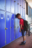 Side view of boy leaning on lockers in corridor. At school Stock Images