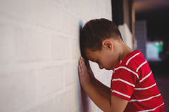 Side view of boy leaning on wall Stock Photo