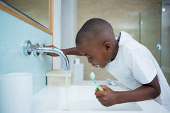Side view of boy spitting while holding brush in sink. At domestic bathroom Stock Photography