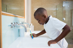 Side view of boy spitting in sink. At bathroom Stock Images