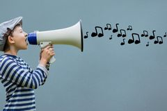 Side view of boy talking in megaphone with musical notes coming out Stock Photo