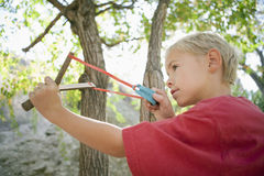 Side View Of Boy Using Slingshot Stock Photo