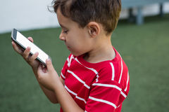Side view of boy using smart phone Royalty Free Stock Photos