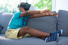 Side view of boy wearing virtual reality headset with arms raised at home Stock Photography