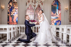 Side view of bridegroom putting ring on surprised bride's finger in church Royalty Free Stock Photography