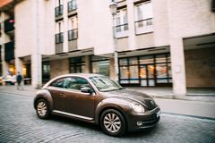Side View Of Brown Volkswagen New Beetle Hatchback Coupe Car In Royalty Free Stock Photography