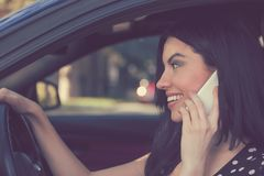 Smiling woman speaking on phone in car royalty free stock photography