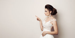 Side view of brunette woman posing at studio and pointing, gesturing by finger at side, looking away. Bride in wedding dress prese Royalty Free Stock Photography