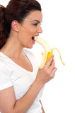 Side view of brunette women eating banana Royalty Free Stock Photo