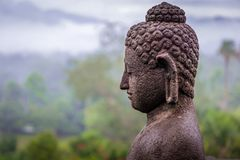 Side view of Buddha statue on a misty morning at Borobudur Temple royalty free stock photography