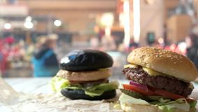 Side view of burgers. Bun, meat, cheese and vegetables. Fast food meal deals stock footage