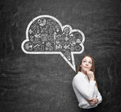 Side view of business lady, student, who is thinking about new business concepts. Drawn cloud with business icons on the black chalkboard royalty free stock photo