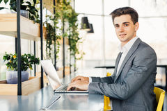 Side view of business man sitting by the table with laptop computer and looking at camera. Side view of Smiling business man sitting by the table with laptop Royalty Free Stock Photos