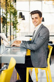 Side view of business man sitting by the table with laptop computer and looking at camera. Side view of Smiling business man sitting by the table with laptop Stock Image