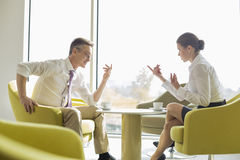 Side view of business people conversing at lobby stock photo