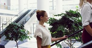Business people moving upstairs on a escalator in office 4k. Side view of Business people moving upstairs on a escalator in office. They are looking away 4k stock footage