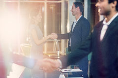 Side view of business people shaking hands with colleagues. 3D Side view of businessmen shaking hands with colleagues in office Stock Photography