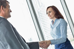 Side view of business people shaking hands in office stock photography