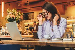 Side view. Business woman is sitting in cafe in front of laptop and looks at screen in surprise, lowering her glasses. Side view. Young business woman is Royalty Free Stock Photography