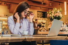 Side view. Business woman is sitting in cafe in front of laptop and looks at screen in surprise, lowering her glasses. Side view. Young business woman is Stock Image