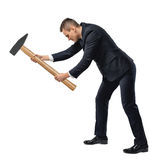 Side view of businessman with big hammer in his arms destroying something, isolated on white background Stock Images