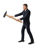 Side view of businessman with big hammer in his arms destroying something, isolated on white background Stock Photography