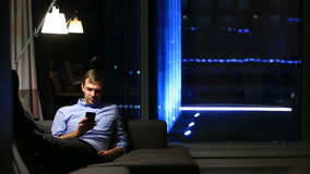 Side view of the businessman browsing the internet using phone. Real time. panoramic window and night city on background stock video footage