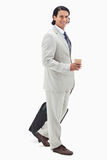 Side view of businessman with coffee and wheely bag Royalty Free Stock Images