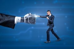 Side view of businessman fighting big robot hand, bright white spark appearing at place where they touch. Human mind vs artificial intelligence. Professional stock image