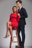Side view of businessman holding seated woman in red dress Stock Photography