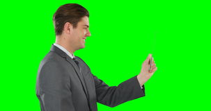 Side view of businessman pretending to use digital tablet. On green background stock video footage