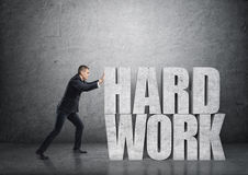Side view of a businessman pushing big 3d concrete 'hard work' words Stock Photos