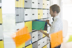 Side view of businessman putting files in locker at creative office Royalty Free Stock Image
