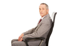 Side view of businessman sitting on armchair Stock Image