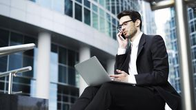 Side view of a businessman sitting with a laptop and talking on phone outside stock video footage
