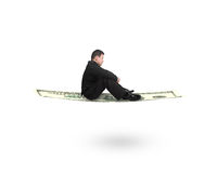 Side view businessman sitting on money flying carpet Stock Images