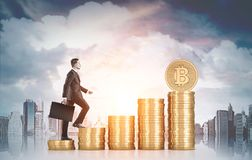 Businessman climbing stacks of bitcoins, city. Side view of a businessman with a suitcase climbing stacks of bitcoins in large city. Mock up toned image Stock Images
