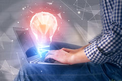 Idea concept. Side view of businessman using laptop with abstract polygonal lamp on white brick wall background. Idea concept. 3D Rendering stock image