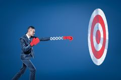 Side view of businessman wearing red boxing gloves and holding out one hand towards big round target. royalty free illustration