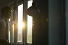 Businessman looking through the window at sunset Royalty Free Stock Photo