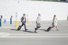 Side view of businesspeople with luggage walking on street Royalty Free Stock Photos